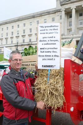 PACEMAKER BELFAST  04/09/2015 Farmers, processers and retailers have held a protest at Stormont to highlight volatility in prices. It was organised by the Ulster Farmers' Union (UFU) and comes ahead of Monday's key EU farm ministers summit on the crisis in the dairy industry. Colm Gibson, a beef and sheep farmer makes his point with a placard outside Stormont. Picture Matt Bohill.