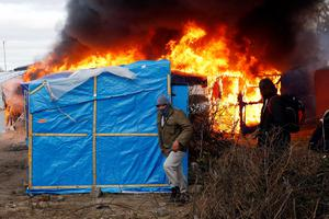 Migrants run past burning tents in a makeshift camp near Calais, France, Monday Feb. 29, 2016. Under the eye of hundreds of riot police, workers began pulling down tents and makeshift shelters in the sprawling camp in Calais on Monday, dismantling the fragile structures that have served as temporary homes for migrants hoping to make their way to a better life in Britain. (AP Photo/Jerome Delay)