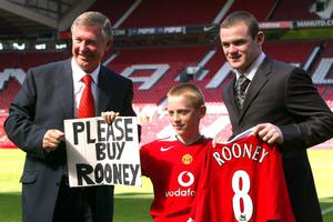 File photo dated 01/09/2004 of Manchester United manager Sir Alex Ferguson (left) and new signing Wayne Rooney (right) with Joe Ruane (centre) who held a sign pleading for the club to sign Rooney at the match against Dinamo Buchrest. PRESS ASSOCITAION Photo. Issue date: Wednesday May 8, 2013. Sir Alex Ferguson will retire at the end of this season, Manchester United have announced. See PA Story SOCCER Man Utd. Photo credit should read: Gareth Copley/PA Wire.