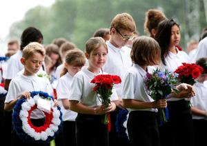 THIEPVAL, FRANCE - JULY 1: School children take part in a procession in the rain holding flowers a wreaths during the Commemoration of the Centenary of the Battle of the Somme at the Commonwealth War Graves Commission Thiepval Memoria on July 1, 2016 in Thiepval, France. The event is part of the Commemoration of the Centenary of the Battle of the Somme at the Commonwealth War Graves Commission Thiepval Memorial in Thiepval, France, where 70,000 British and Commonwealth soldiers with no known grave are commemorated. (Photo bt Yui Mok - Pool/Getty Images)