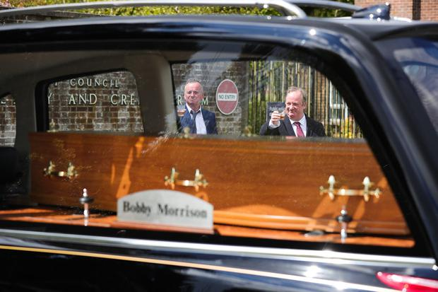 Actors Paddy Jenkins and Damon Quinn join family and friends to raise a toast outside Roselawn Cemetery in Belfast as the hearse arrives during the funeral of actor BJ Hogg.