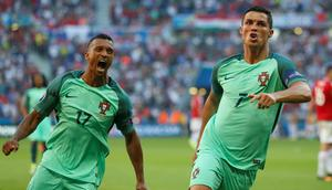 Portugal's Cristiano Ronaldo celebrates with teammate Nani, left, after scoring his side's second goal during the Euro 2016 Group F soccer match between Hungary and Portugal at the Grand Stade in Decines-Charpieu, near Lyon, France, Wednesday, June 22, 2016. (AP Photo/Darko Bandic)