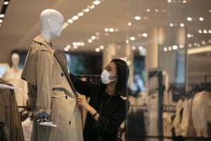 A department store employee dresses a mannequin in Tokyo. Japan is hoping the major factors of its economy, including retail sales, soon begin to recover from the coronavirus pandemic (Jae C. Hong/AP)