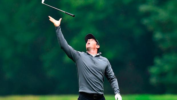 On high: Rory McIlroy throws his iron into the air