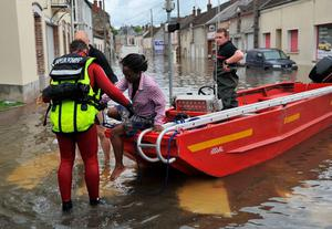 Firefighters help a woman to disembark a boat as the city is flooded due to heavy rainfalls at Montargis, central France, on June 01, 2016. AFP/Getty Images