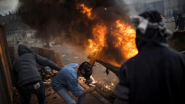 Palestinian youth clash with police at Shuafat refugee camp after a Palestinian resident of the camp was named as the driver of a van that rammed into a crowd at a rail stop on November 5, 2014 in Jerusalem, Israel.  (Photo by Ilia Yefimovich/Getty Images)