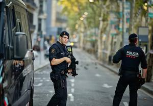 Armed police officers patrol a deserted street in Las Ramblas after the attack on Friday.