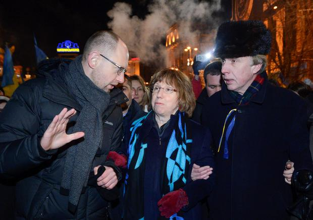 Ukrainian opposition leader Arseniy Yatsenyuk, left, and EU foreign policy chief Catherine Ashton, center, and former Ukrainian Foreign Minister Vladimir Ogryzko, right, arrive to meet Pro-European Union activists gathered on the Independence Square in Kiev, Ukraine, Tuesday, Dec. 10, 2013.