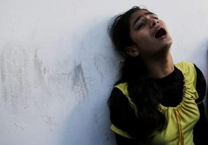 A displaced Palestinian girl who had lost her relative in an Israeli airstrike at a U.N school cries at Beit Hanoun hospital in the northern Gaza Strip, Thursday, July 24, 2014. Israeli tank shells hit a compound housing a UN school in the Gaza Strip on Thursday, killing more than a dozen of people and wounding dozens who were seeking shelter from fierce clashes on the streets outside. (AP Photo/Adel Hana)