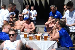 Leicester City's supporters drink beer at a terrace bar on Plaza Mayor before the UEFA Champions League quarter final first leg football match Club Atletico de Madrid vs Leicester City, in Madrid on April 12, 2017. / AFP PHOTO / CURTO DE LA TORRECURTO DE LA TORRE/AFP/Getty Images