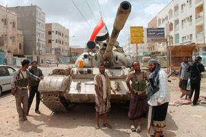 Yemeni members of the southern separatist movement, loyal to President Abedrabbo Mansour Hadi, stand next to a tank on April 15, 2015 in Aden's northern suburbs. Saudi-led coalition air strikes hit rebel targets in the Yemen's main southern city after overnight attacks by anti-government forces killed seven people, military sources and medics said. AFP/Getty Images