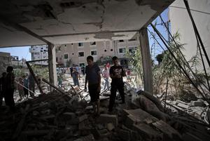 Palestinians inspect the rubble of a destroyed house following an Israeli strike killing Christian woman Jalila Ayyad, 70, in Gaza City on Sunday, July 27, 2014. (AP Photo/Khalil Hamra)