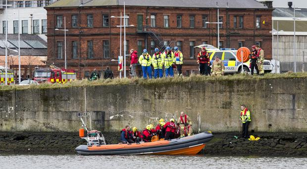Emergency teams help rescue the woman on the banks of the River Lagan. Pic Liam McBurney/RAZORPIX