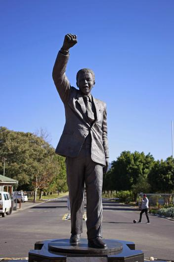 A boy kicks a ball behind a statue of former South African President Nelson Mandela outside the Groot Drakenstein correctional facility near the town of Franschhoek, South Africa, Sunday, June 9, 2013. (AP Photo/Schalk van Zuydam)
