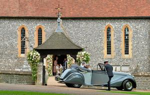 ENGLEFIELD GREEN, ENGLAND - MAY 20: Britain's Catherine, Duchess of Cambridge (L), stands with pageboys and bridesmaids in the doorway of St Mark's Church as her sister Pippa Middleton arrives with their father Michael Middleton in a vintage Jaguar for her wedding to James Matthews at St Mark's Church on May 20, 2017 in Englefield Green, England.  (Photo by Justin Tallis - WPA Pool)