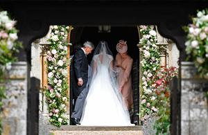 ENGLEFIELD GREEN, ENGLAND - MAY 20: Britain's Catherine, Duchess of Cambridge (R), adjusts the dress of her sister Pippa Middleton as their father, Michael Middleton (L) stands by at the door to the church ahead of Pippa's wedding to James Matthews at St Mark's Church on May 20, 2017 in Englefield Green, England.  (Photo by Justin Tallis - WPA Pool)