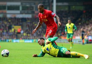 NORWICH, ENGLAND - APRIL 20:  Nathan Redmond of Norwich City clashes with Glen Johnson of Liverpool during the Barclays Premier League match between Norwich City and Liverpool at Carrow Road on April 20, 2014 in Norwich, England.  (Photo by Jamie McDonald/Getty Images)