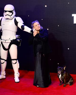 File photo dated 16/12/2015 of Carrie Fisher Carrie Fisher with her dog Gary as she arrives to the Star Wars: The Force Awakens European Premiere, as the actress has died at age 60, her daughter's publicist said. PRESS ASSOCIATION Photo. Picture date: Tuesday December 27, 2016. See PA story DEATH Fisher. Photo credit should read: Anthony Devlin/PA Wire