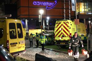 Ambulance crews attend a major incident after up to 60 young people attending a concert at the Odyssey Arena, Belfast, Northern Ireland were taken ill and treated for the effects of drugs and alcohol, Thursday, Feb. 6, 2014. The incident happened at a dance event by Dutch DJ Hardwell. (AP Photo/Peter Morrison)