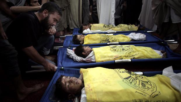 Palestinians mourn over the lifeless bodies of four boys from the same extended Bakr family (AP Photo/Khalil Hamra)
