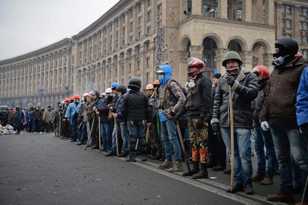 KIEV, UKRAINE - FEBRUARY 20:  Anti-government protesters prepare to push forward during continued clashes with police in Independence square, despite a truce agreed between the Ukrainian president and opposition leaders on February 20, 2014 in Kiev, Ukraine. After several weeks of calm, violence has again flared between police and anti-government protesters, who are calling to oust President Viktor Yanukovych over corruption and an abandoned trade agreement with the European Union.  (Photo by Jeff J Mitchell/Getty Images)