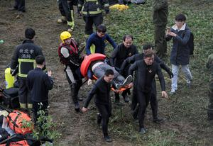 Emergency personnel carry the body of a passenger extracted from a commercial plane after it crashed in Taipei, Taiwan, Wednesday, Feb. 4, 2015. The Taiwanese commercial flight with 58 people aboard clipped a bridge shortly after takeoff and crashed into a river in the island's capital of Taipei on Wednesday morning.  (AP Photo/Wally Santana)