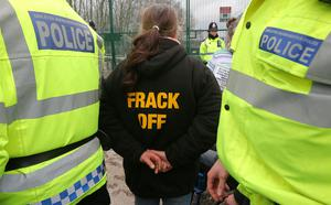 Police officers walk past a protester at the gates of the Barton Moss exploration facility on March 6, 2014 in Barton, England. Campaigners, who have been on the site in Barton Moss Road since November last year, are awaiting a court decision as to whether they are to be lawfully evicted. (Photo by Dave Thompson/Getty Images)