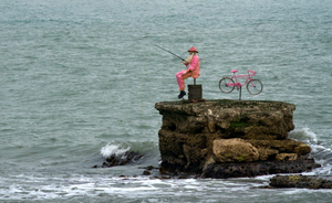 A Giro d'Italia pink sculpture of a man fishing which can be seen just off the Coast Road in Glenariffe in the Glens of Antrim