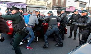 Police clash with bystanders after a car is driven into a crowd outside Ardoyne shops, trapping a girl underneath the car in north Belfast, Northern Ireland on July 13, 2015.