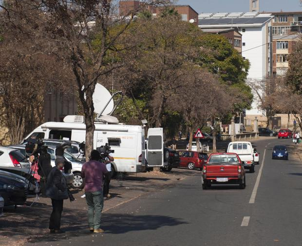 Press gather outside the hospital in Pretoria, South Africa, where Nelson Mandela was hospitalized with a recurring lung infection early Saturday, June 8, 2013. A presidential statement said that Mandela was in a serious but stable condition. (AP Photo)