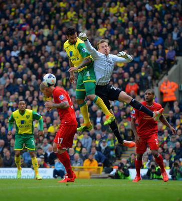 NORWICH, ENGLAND - APRIL 20: Simon Mignolet of Liverpool fails to punch the ball clear during the Barclays Premier League match between Norwich City and Liverpool at Carrow Road on April 20, 2014 in Norwich, England.  (Photo by Michael Regan/Getty Images)