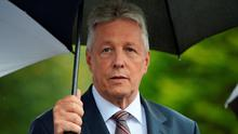 Northern Ireland First Minister and DUP leader Peter Robinson looks from under his umbrella at Stormont castle as he holds a press conference on September 14, 2015 in Belfast, Northern Ireland. (Photo by Charles McQuillan/Getty Images)