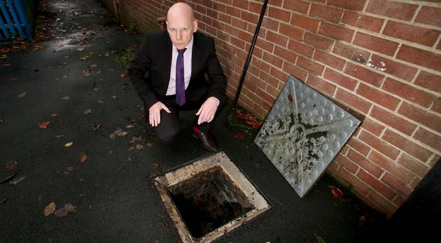 Holy Cross principal Kevin McArevey looks into the drain where the weapon was found
