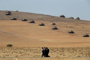 Turkish Kurds walk as tanks in the background hold their positions on a hilltop in the outskirts of Suruc, at the Turkey-Syria border, overlooking Kobani in Syria where fighting had ben intensified between Syrian Kurds and the militants of Islamic State, Monday, Oct. 6, 2014. Kobani, also known as Ayn Arab and its surrounding areas have been under attack since mid-September, with militants capturing dozens of nearby Kurdish villages.(AP Photo/Lefteris Pitarakis)