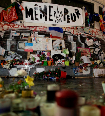 """A banner reading """"not even afraid"""" (meme pas peur), along with flowers, candles, drawings and notes, is pictured at the Republic monument during a ceremony in homage to the victims of the January 2015 Paris attacks"""