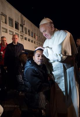Pope Francis touches the head of a migrant during his visit at the Castelnuovo di Porto refugees center near Rome on March 24, 2016.
