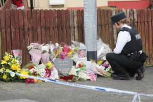 PRESS EYE BELFAST - 19/4/19-  PSNI officer lays floral tributes left by members of the public  following the murder of 29-year-old Lyra McKee during rioting after police searches in the area last night.