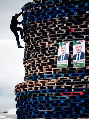 BELFAST, NORTHERN IRELAND - JULY 10:  A Loyalist climbs the Conway street bonfire built in preparation for the 11th night bonfire on July 10, 2017 in Belfast, Northern Ireland. Tradition holds that the bonfires commemorate the lighting of fires on the hills to help Williamite ships navigate through Belfast Lough at night when Protestant King William III and his forces landed at Carrickfergus to fight the Catholic Jacobites, supporters of the exiled Catholic King James II. The bonfires also mark the beginning of the annual 12th of July Orange parades.   (Photo by Jeff J Mitchell/Getty Images) ***BESTPIX***