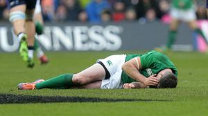 Johnny Sexton lies prone on the turf at Murrayfield (Graham Stuart/PA)