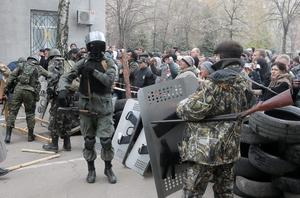 Armed pro-Russian activists occupy the police station carrying riot shields as people watch on, in the eastern Ukraine town of Slovyansk on Saturday, April 12, 2014. Pro-Moscow protesters have seized a number of government buildings in the east over the past week, undermining the authority of the interim government in the capital, Kiev. (AP Photo/Efrem Lukatsky)