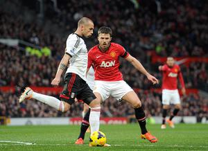 Fulham's Johnny Heitinga (left) passes the ball in front of Manchester United's Michael Carrick during the Barclays Premier League match at Old Trafford, Manchester.