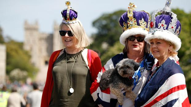 Royal fans bedecked with Union flags and crowns pose along the Long Walk in Windsor the day before the Royal wedding (AFP PHOTO / Odd ANDERSENODD ANDERSEN/AFP/Getty Images)