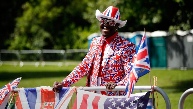 Royal fan Joseph Afrane, bedecked in Union flag colours, poses along the Long Walk in Windsor on May 18, 2018, the day before the Royal wedding.  Britain's Prince Harry and US actress Meghan Markle will marry on May 19 at St George's Chapel in Windsor Castle. / AFP PHOTO / Tolga AKMENTOLGA AKMEN/AFP/Getty Images