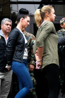 Police escort Michaella McCollum Connolly (left) and Melissa Reid in handcuffs as they are moved from the National Police anti-drug headquarters to a court to be formally charged for drug trafficking in Lima, Peru, Tuesday, Aug. 20, 2013