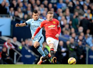 Manchester City's Sergio Aguero battles for the ball with Manchester United's Wayne Rooney (right) during the Barclays Premier League match at the Etihad Stadium, Manchester. Martin Rickett/PA Wire.