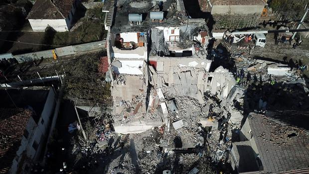 Rescuers search at a damaged building after the magnitude 6.4 earthquake (Hektor Pustina/AP)
