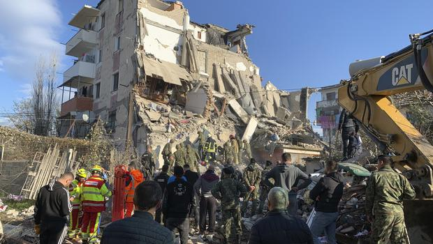 Rescuers search at a damaged building in Thumane (Visar Kryeziu/AP)