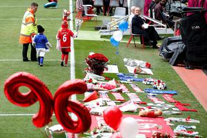 Children lay flowers on the pitch during the last memorial service to be held at Anfield, Liverpool, to mark 27 years to the day since the tragedy claimed 96 lives. PRESS ASSOCIATION Photo. Picture date: Friday April 15, 2016. The 96 Liverpool fans died in the crush on the Leppings Lane terraces at Sheffield Wednesday's Hillsborough stadium after going to see their team play Nottingham Forest in an FA Cup semi-final on April 15, 1989. See PA story MEMORIAL Hillsborough. Photo credit should read: Peter Byrne/PA Wire