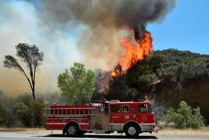 Flames rise from a wildfire near Clearlake, Calif., Monday, Aug. 3, 2015. Officials called for evacuations Monday as numerous homes were threatened by the flames. (AP Photo/Josh Edelson)