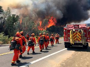 Fire crews walk on U.S. Highway 20 as a fire approaches near Clearlake, Calif., Monday, Aug. 3, 2015. Cooler weather helped crews build a buffer Monday between a raging Northern California wildfire and some of the thousands of homes it threatened as it tore through drought-withered brush that hadn't burned in years. (AP Photo/Terry Chea)
